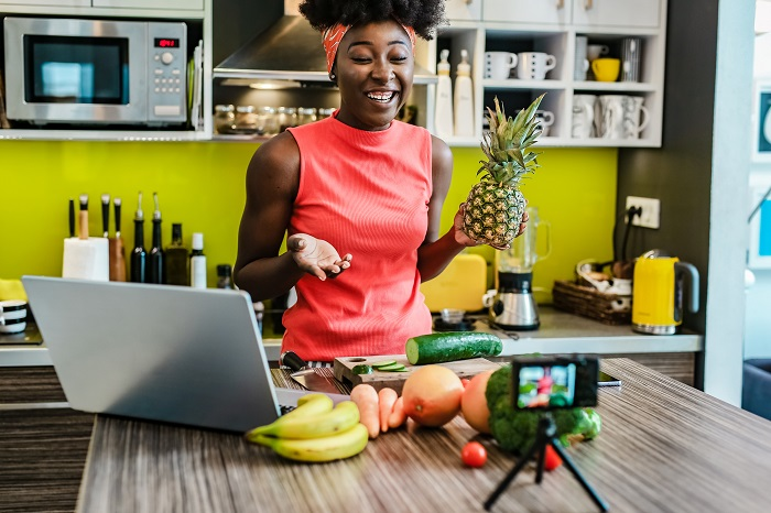 Photo of female content creator filming in her kitchen to represent content creation for brand awareness.